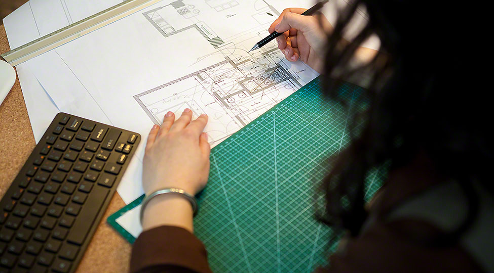 Architect working on blueprints on her table