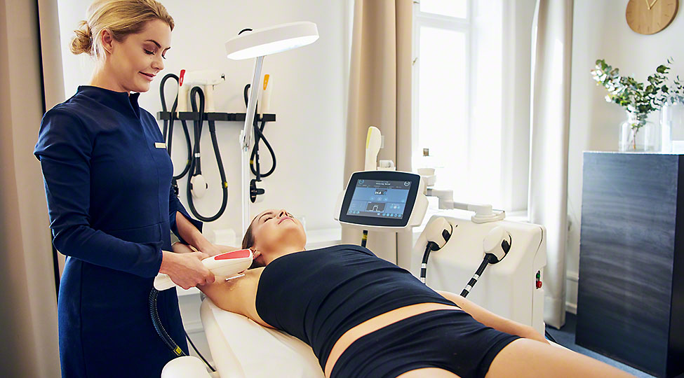 Beauty clinic technician performing electrolysis on a female client