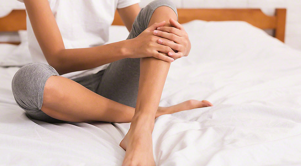 Bodycare. Woman with bare legs sitting on bed