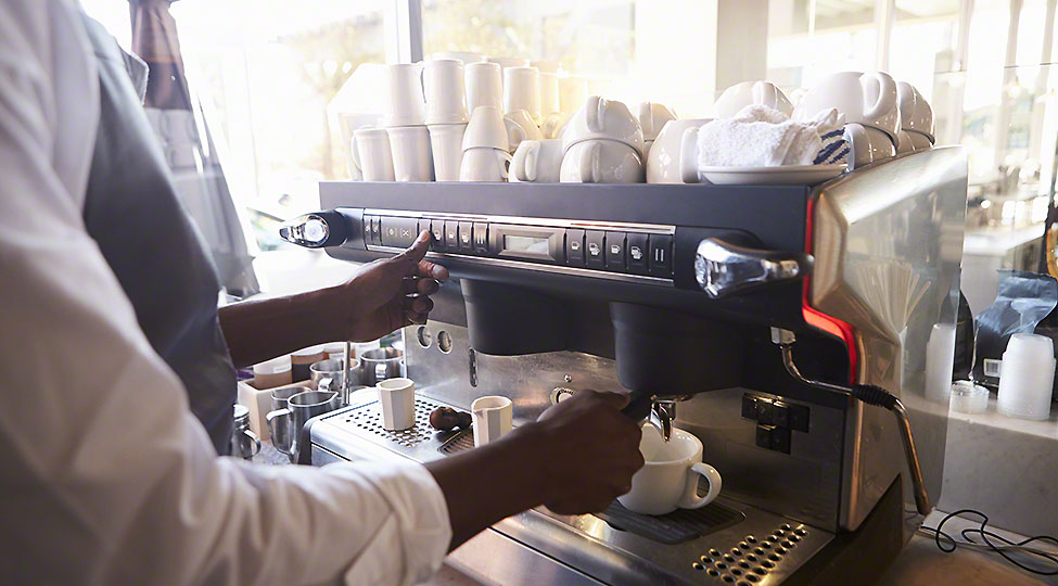Close Up Of Barista Making Coffee In Deli Using Machine