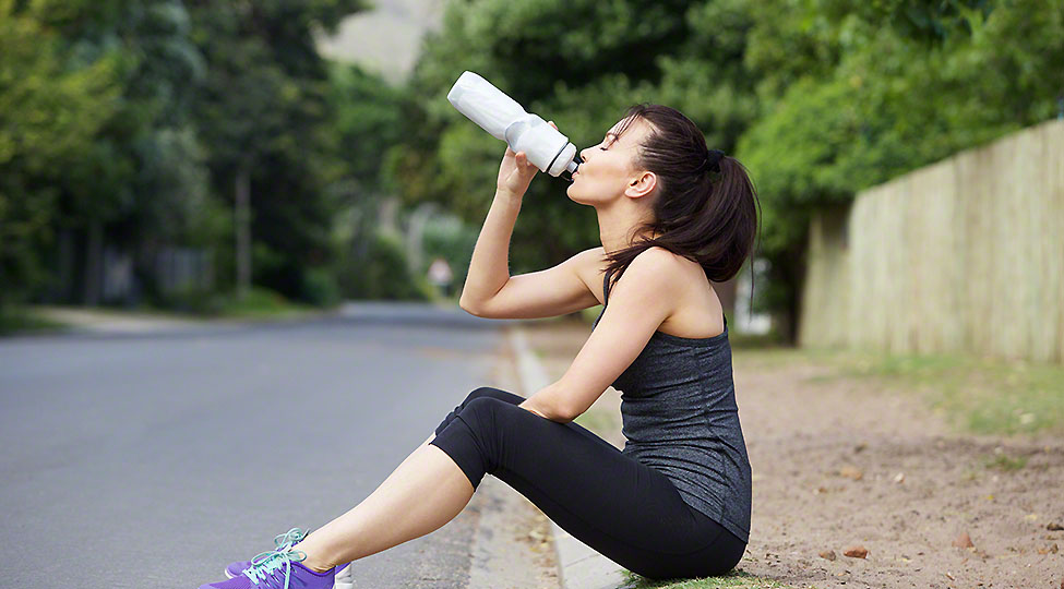 Fit young lady drinking water after workout
