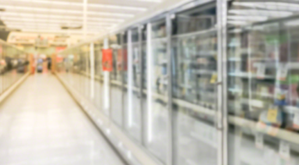 Blurry background low angle view transparent fridge with frozen food section at grocery store