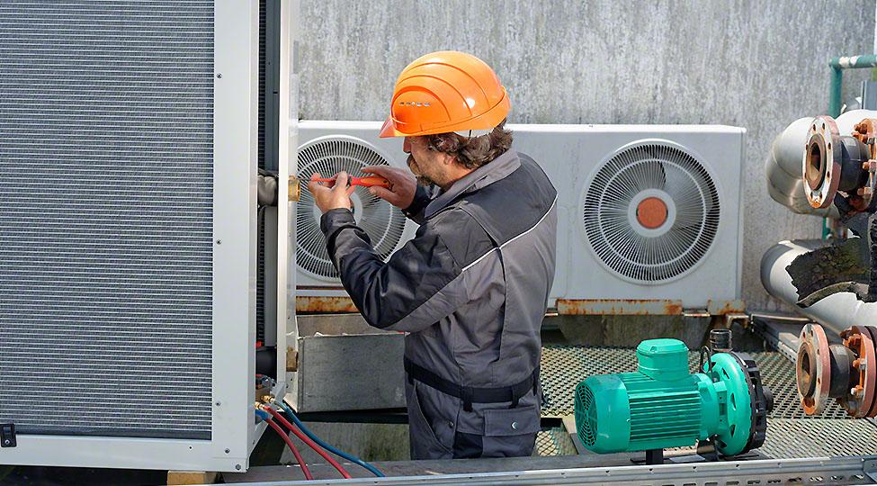 An man in a hard-hat repairing an air conditioning