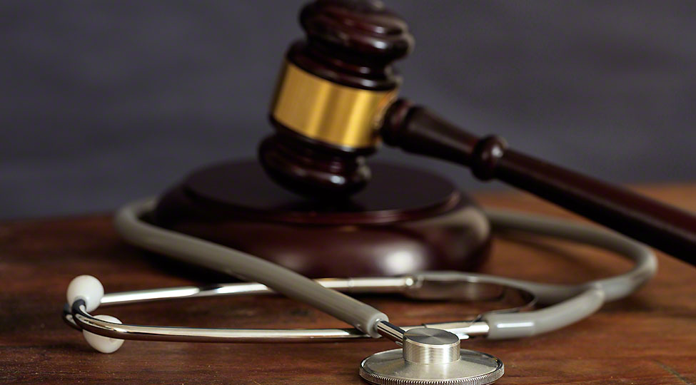 Judge gavel and a stethoscope on a wooden desk