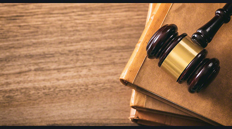 Judge gavel on law books, wooden desk, top view