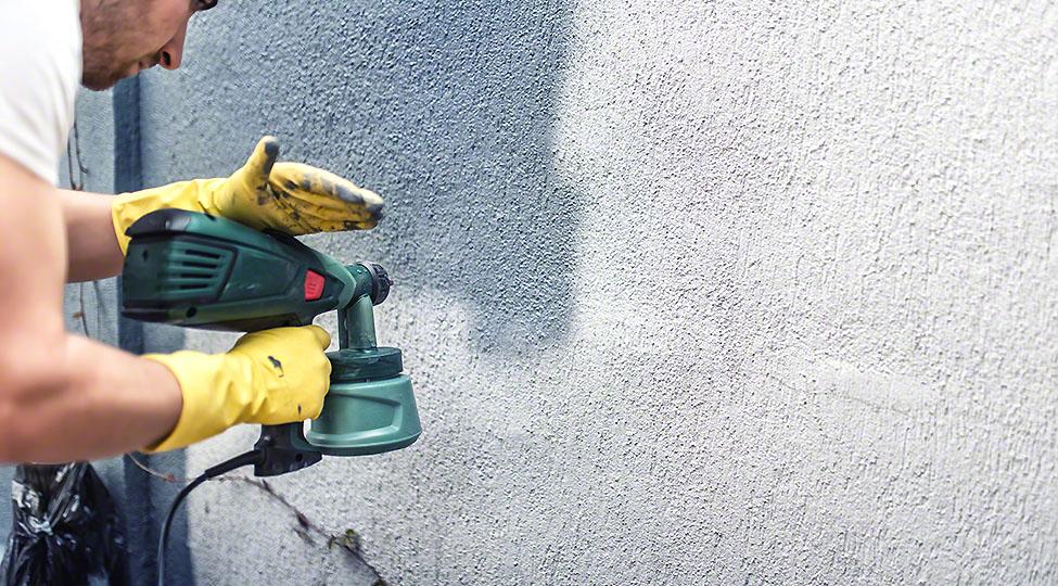 Man painting a grey wall, renovating exterior walls of new house