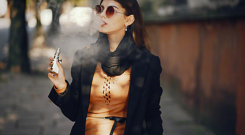 stylish girl smoking an e-cigarette