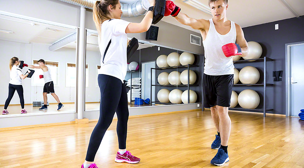 Two focused people training boxing at the fitness gym