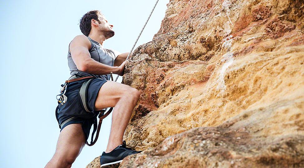 Young man climbing natural rocky wall