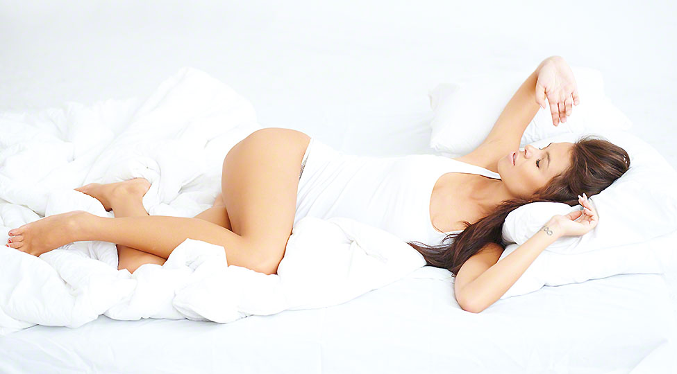 Young sexy girl lying on white bed